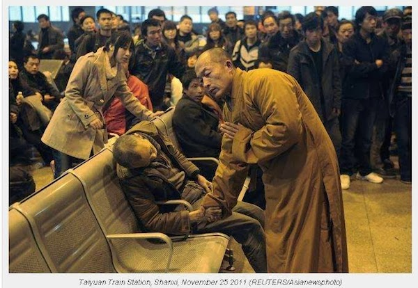 A_monk_prays_for_a_dead_man_in_the_station_hall_of_the_Shanxi_Taiyuan_Train_Station_China.jpg